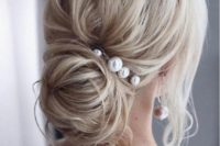 11 a wavy low bun with a volume on top and some locks down accented with large pearl pins and matching earrings