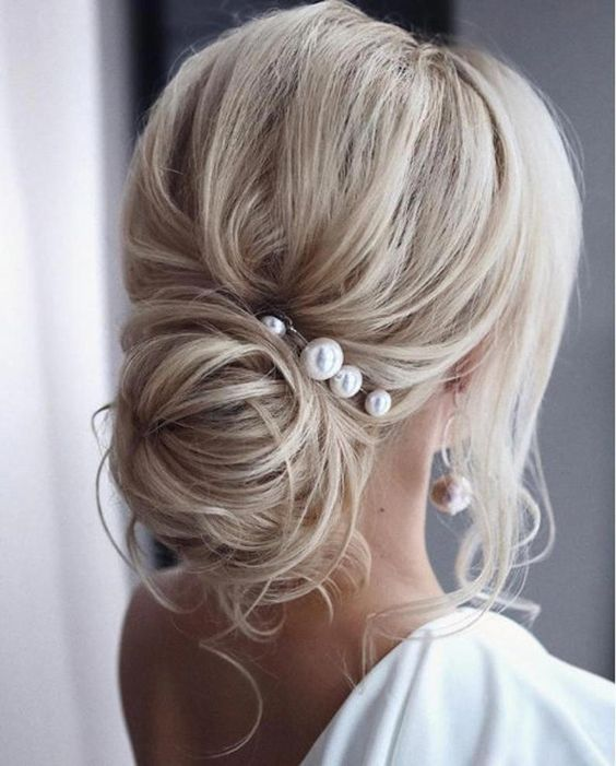 a wavy low bun with a volume on top and some locks down accented with large pearl pins and matching earrings