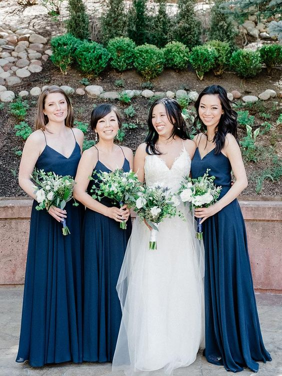 simple navy spaghetti strap maxi dresses and greenery and white bloom bouquets for a chic and bold navy and green wedding