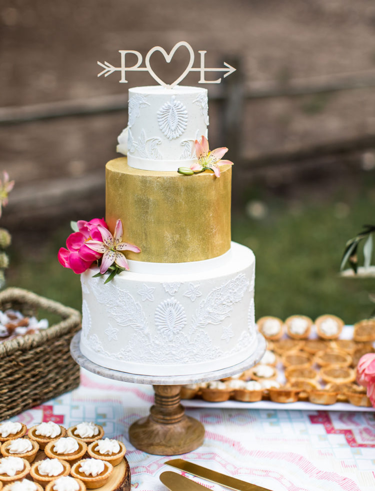 The wedding cake was whimsy, with a gold and white lace tiers, an arrow topper and pink blooms