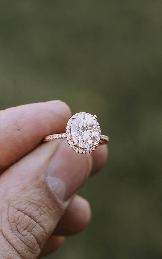 a rose gold engagement ring with an oval shaped diamond and a halo around