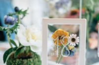 12 a stylish table number with pressed flowers and a leaf in a frame and a stand is a cool idea for wedding tables
