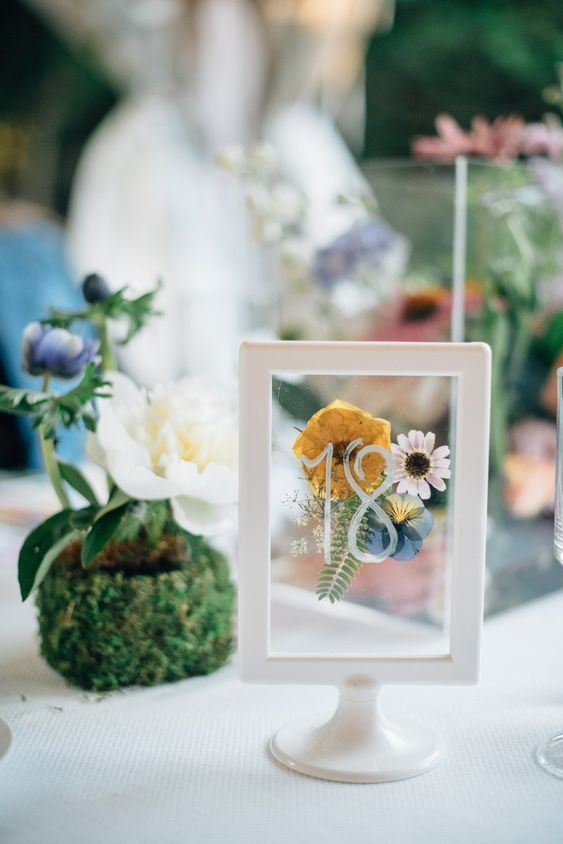 a stylish table number with pressed flowers and a leaf in a frame and a stand is a cool idea for wedding tables