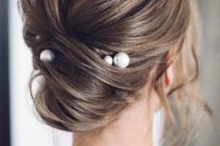 12 an effortlessly chic twisted updo with a volume on top and some locks down accented with large pearl pins