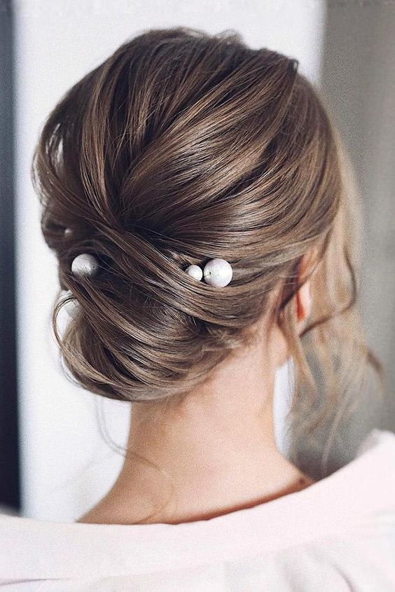 an effortlessly chic twisted updo with a volume on top and some locks down accented with large pearl pins