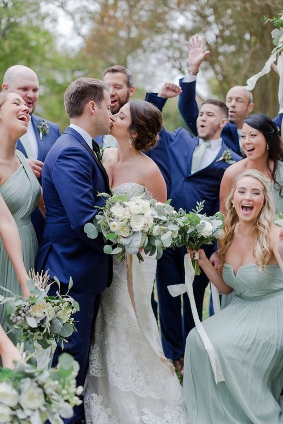 groomsmen wearing navy suits and sage green ties and bridesmaids wearing sage green strapless dresses