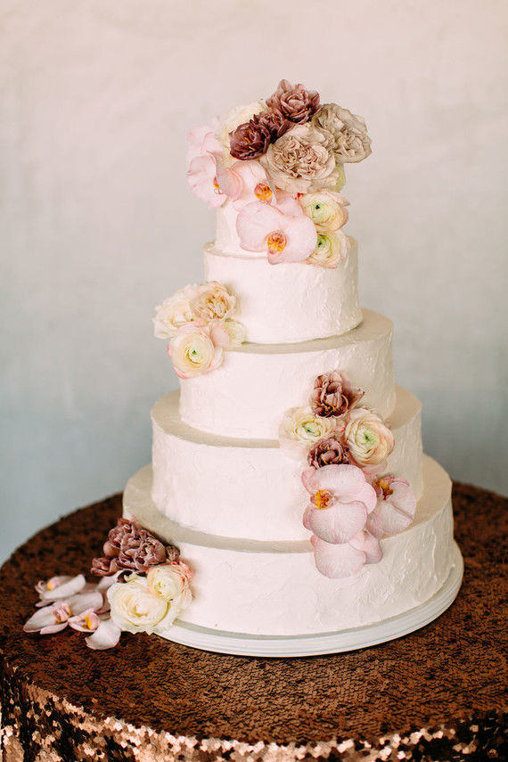 The wedding cake was white and textural, decorated with mauve and pink blooms