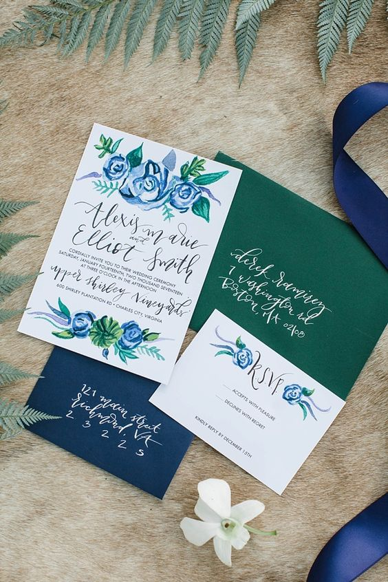 a beautiful navy and green wedding invitation suite with painted blue flowers and a silk ribbon