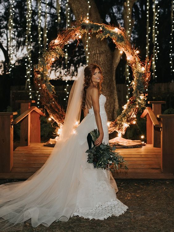 a round wedding arch decorated with dried greenery and herbs, twigs and lights for a chic look with a rustic feel