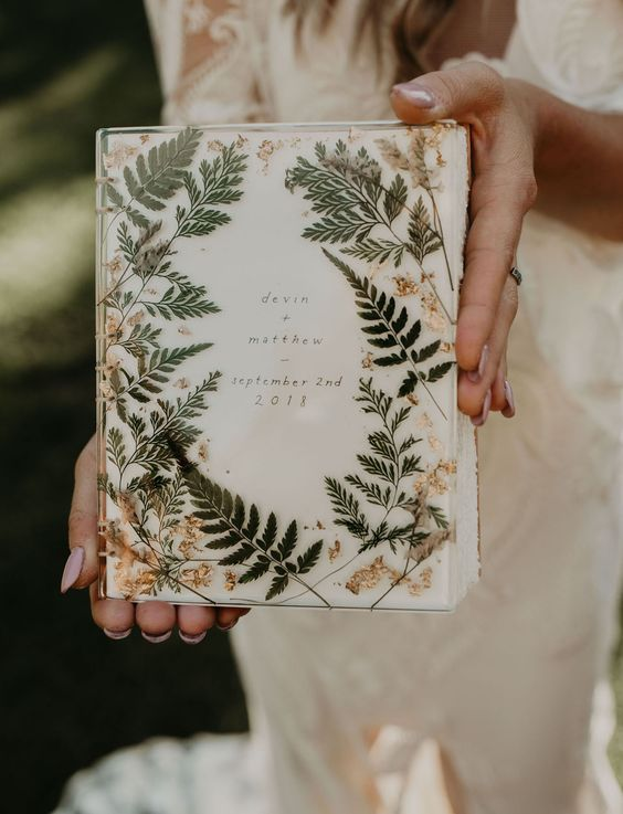 a wedding album done with pressed leaves and gold leaf loooks very chic and very nice