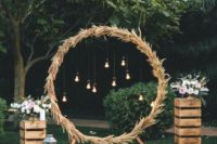 15 a round wedding arch fully covered with pampas grass and with bulbs hanging inside plus blooms and candles on crates