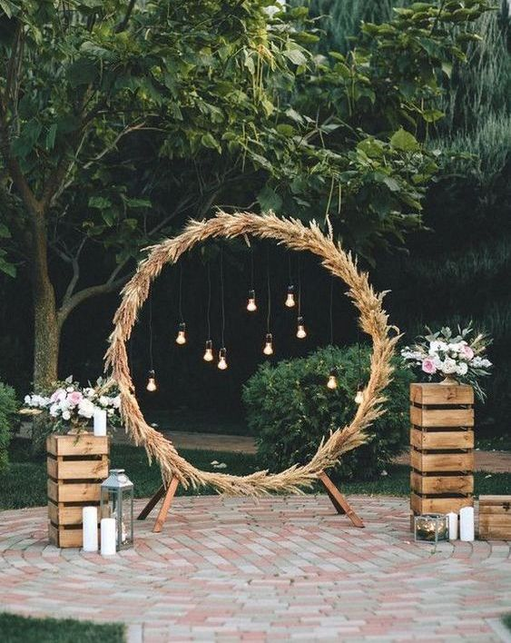 a round wedding arch fully covered with pampas grass and with bulbs hanging inside plus blooms and candles on crates