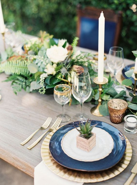 a chic and bright wedding tablescape with navy plates, a lush greenery and white bloom table runner, touches of gold