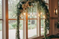 16 a rounded wedding arch fully covered with greenery and white blooms and some bulbs hanging down for an accent