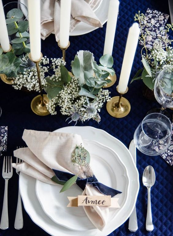 a chic table setting with a navy quilted tablecloth, pale greenery and white blooms, tall candles and white porcelain