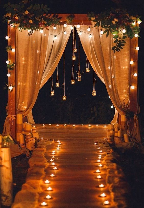 a simple and cool wedding arch with burlap curtains, string lights, candleholders hanging down and candles lining up the aisle