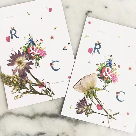 wedding invitations with pressed blooms and greenery and petals look bold and chic