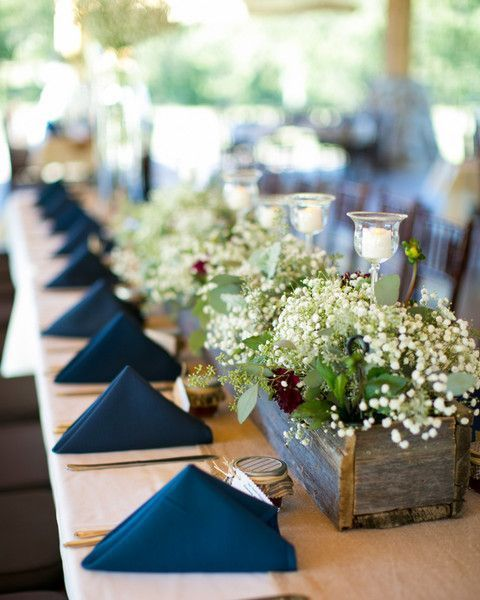 a reception table done with navy napkins, a greenery and neutral bloom centerpiece, candles and simple cutlery
