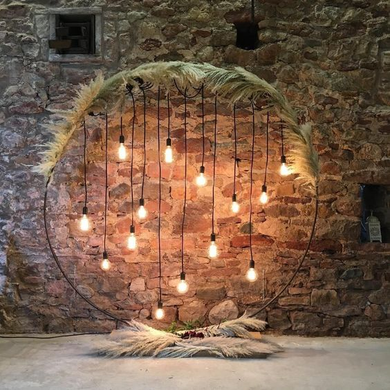 a simple and stylish round wedding arch covered with pampas grass and with bulbs hanging down is a chic idea