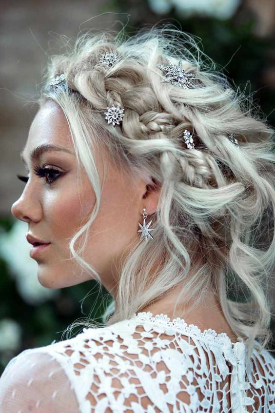 a braided messy updo accented with rhinestone star hair pins and matching earrings for a celestial bride