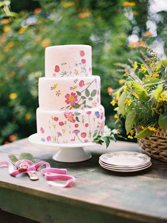 a bright summer wedding cake - a white one with pressed pink blooms and petals plus greenery