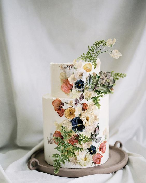 a decadent wedding cake with dried and pressed flowers plus foliage is a gorgeous idea for many wedding styles