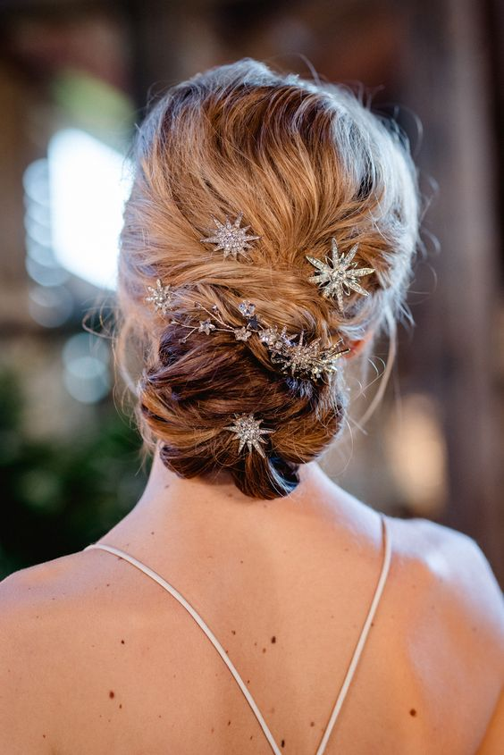 a messy and textural low bun accented with star and flower rhinestone hairpins for a chic modern look