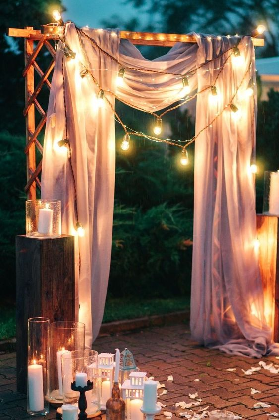 a simple wedding arch draped with pink fabric, string lights, with lots of candles and candle lanterns around it