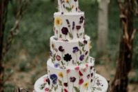 22 a large white wedding cake with colorful pressed blooms and leaves is a chic and bold idea to go for