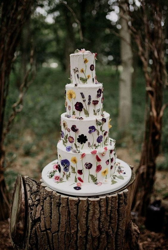a large white wedding cake with colorful pressed blooms and leaves is a chic and bold idea to go for