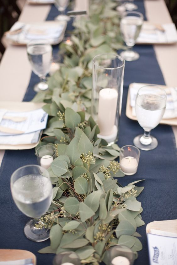 a simple and stylish reception table with a navy runner, a lush eucalyptus one, white candles and simple glasses