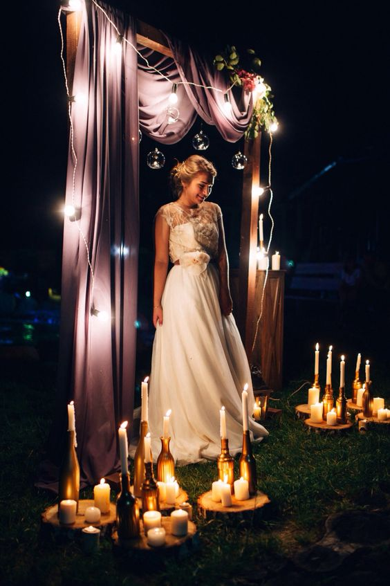 a wedding arch done with mauve fabric, string lights and greenery and blooms plus lots of candles on the ground