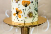 23 a mini white wedding cake with pressed blooms and greenery is a very bold and chic idea for spring, summer and fall