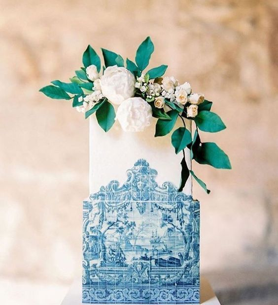 a square wedding cake styled as azulejo in blue and white and topped with greenery and neutral blooms