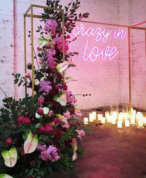 a beautiful wedding ceremony space with candles, an arch, lush florals in red, burgundy and pink and a pink neon sign