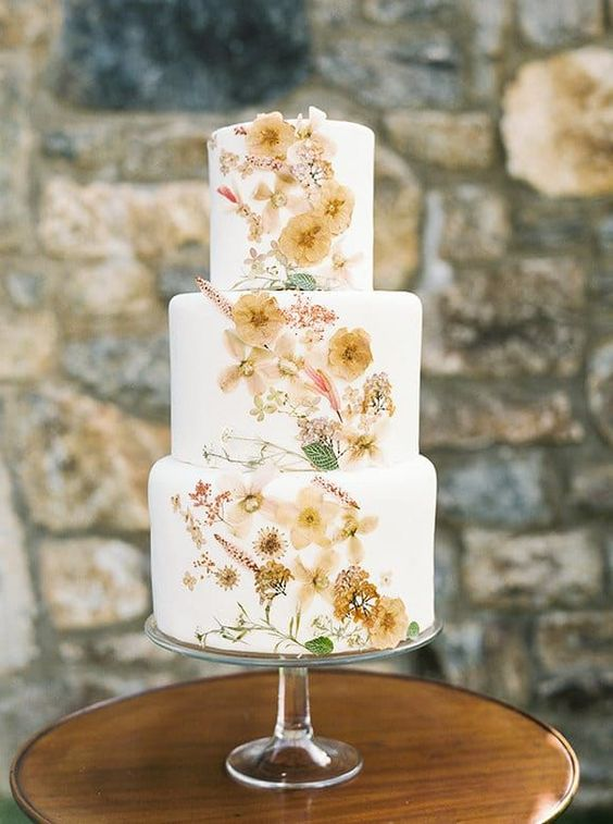 a swoon-worthy wedding cake with pressed blooms and greenery in neutral shades is a tender idea