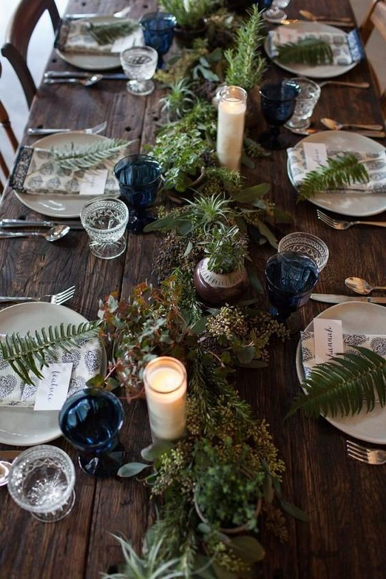 a woodland wedding table with a greenery and air plant runner, pillar candles, ferns and blue glasses