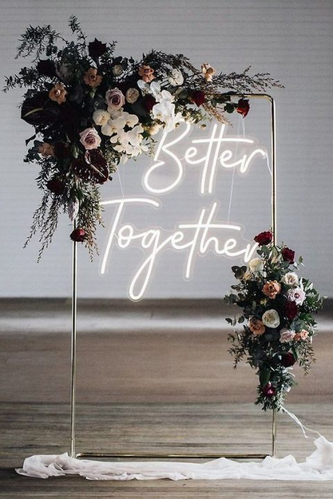 a chic wedding arch of metal, with lush blooms and greenery and a neon sign for a modern wedding