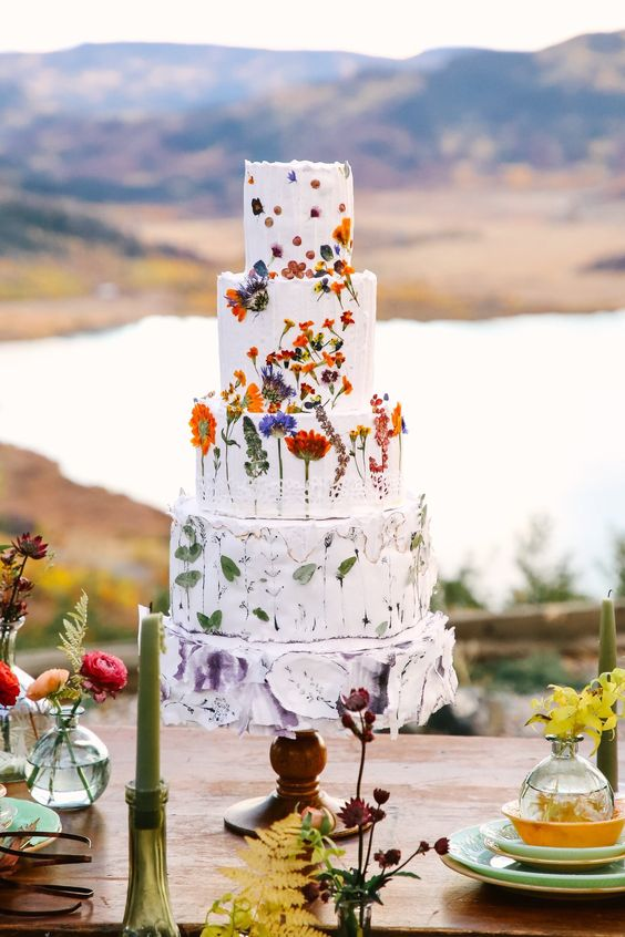 a textural white wedding cake was done with pressed flowers and greenery is a bold and fun idea for a summer wedding