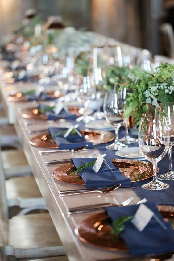 an elegant and bright wedding tablescape with lush greenery, a navy table runner and napkins and touches of copper