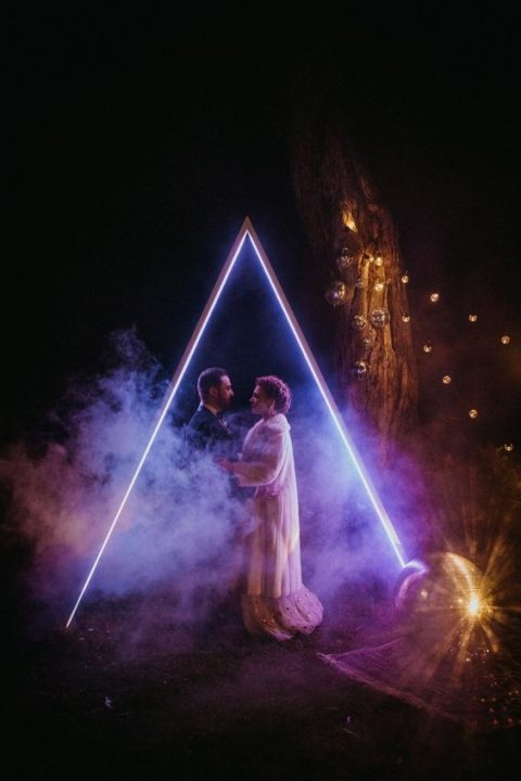 a fantastic neon geometric wedding arch looks just jaw-dropping, it's ideal for an evening or night ceremony and to take pics