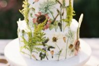 26 a wild-looking wedding cake with pressed blooms and greenery plus some fresh branches