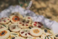27 an assortment of sugar cookies with pressed dried blooms and foliage is a stylish and very cute idea for a wedding