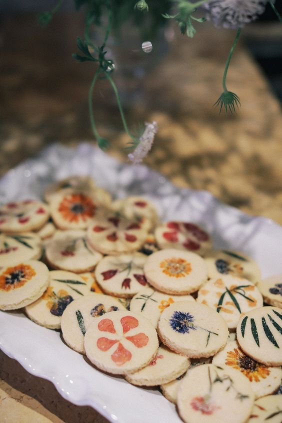 an assortment of sugar cookies with pressed dried blooms and foliage is a stylish and very cute idea for a wedding