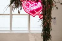 28 a lush greenery and bright pink blooms wedding arch with a large pink neon heart is a stunning modern idea