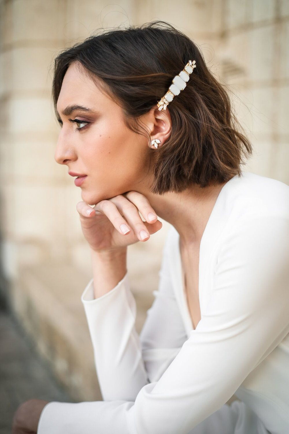 an elegant modern barrette with white rhinestones and gold plus matching stud earrings for a modern bride