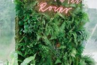29 a lush greenery wall with a red neon sign is a very fresh and cool wedding decor idea