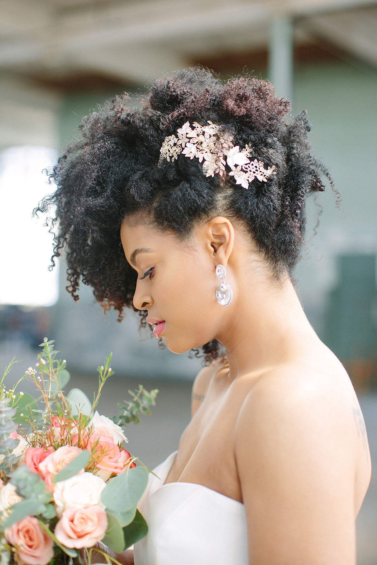 natural curls raised up and accented with gold flowers looks veyr refined, chic and bold