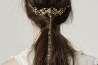 30 a messy low ponytail with a gold floral hair vine with long chains and rhinestons