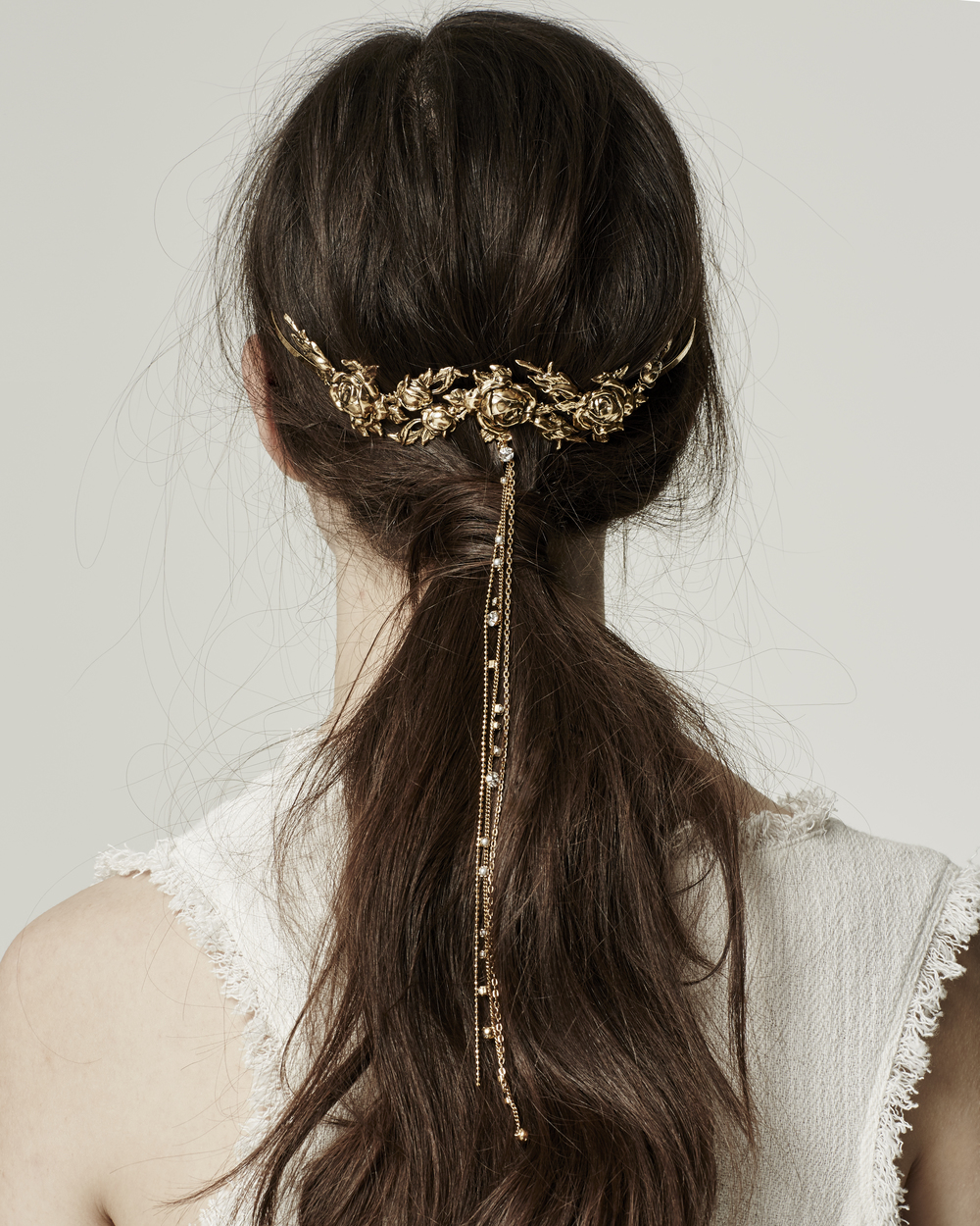 a messy low ponytail with a gold floral hair vine with long chains and rhinestons